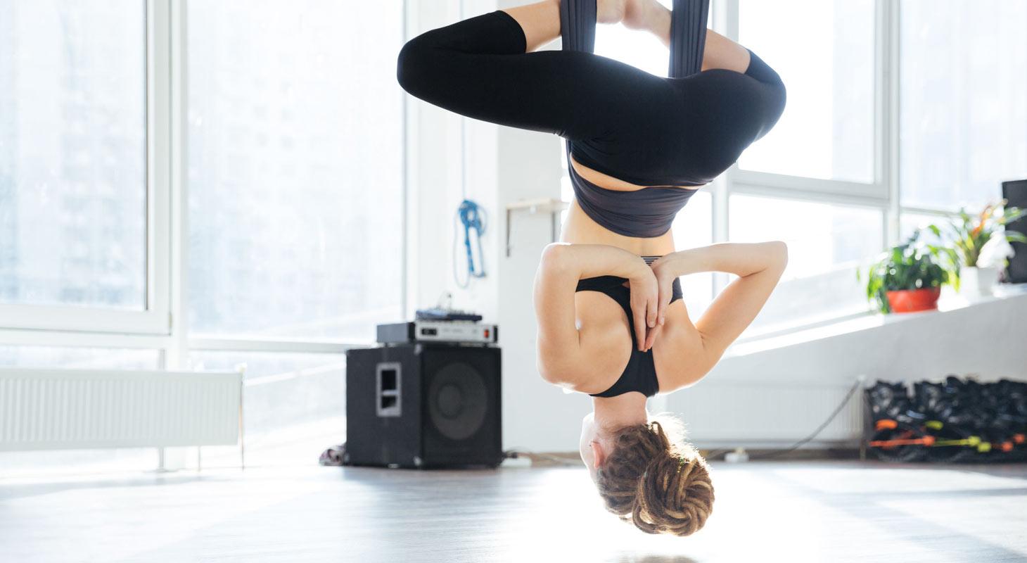 Femme dans un studio pratiquant l'aero yoga