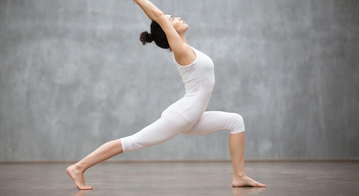 Femme en tenue blanche faisant du yoga dans la position du guerrier 1