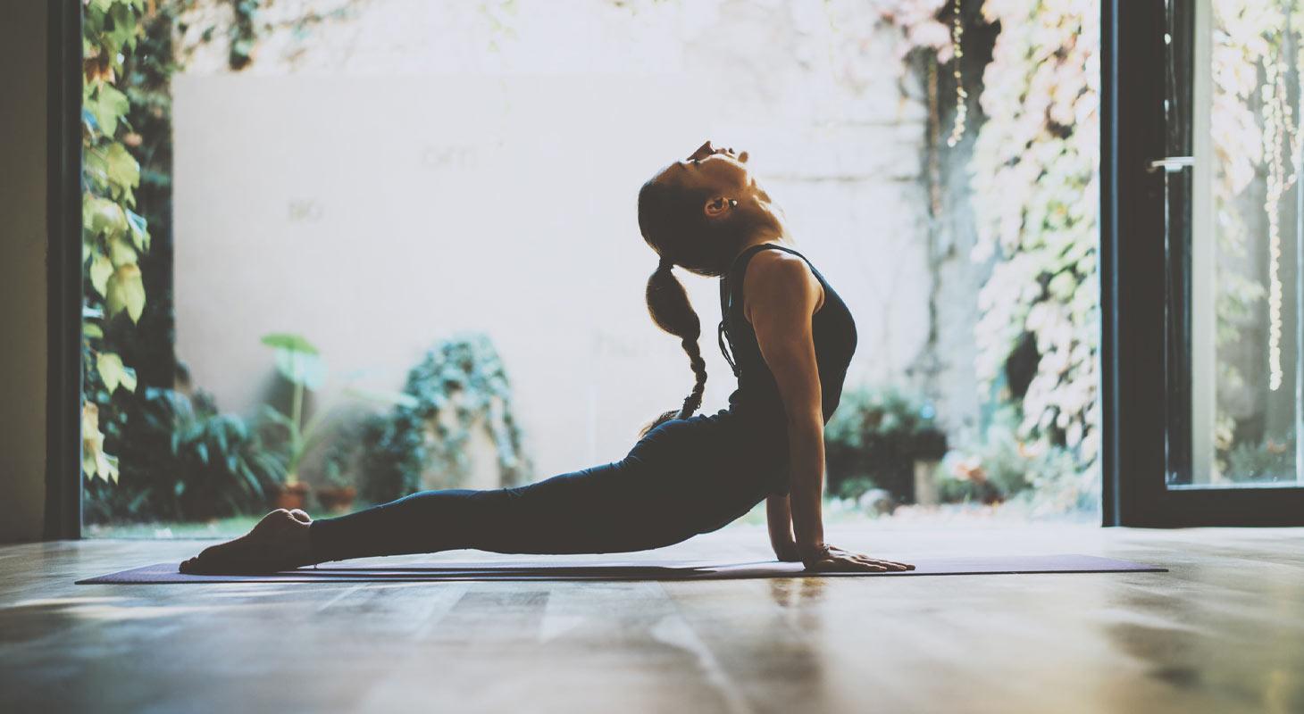 Femme pratiquant le yoga dans la position du chien tête en haut