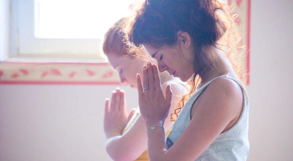 Femmes dans un cours de yoga méditent en faisant le gest du namasté