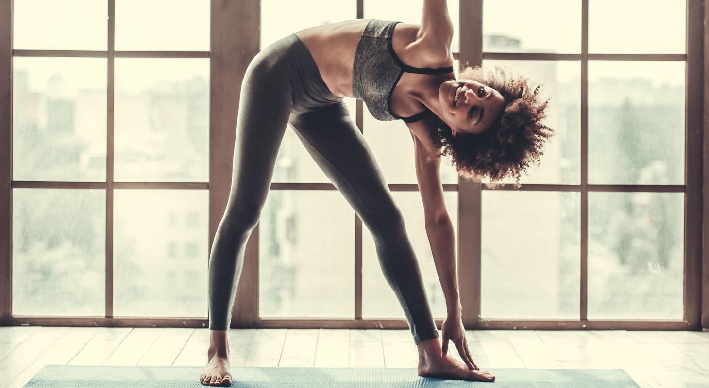 Jolie fille afro en vêtements de sport fait du yoga en souriant