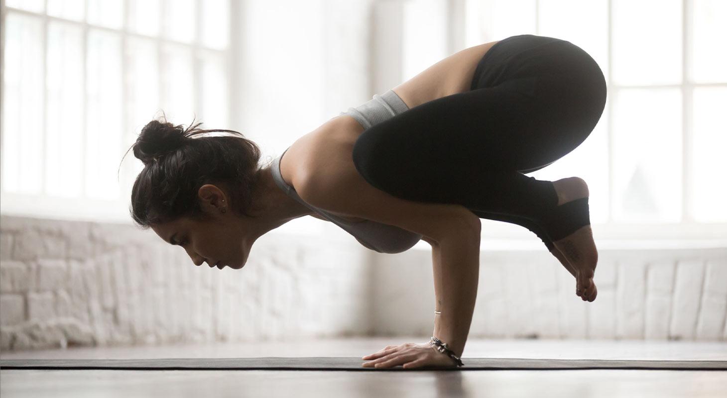 Femme faisant du yoga en studio dans la position du corbeau