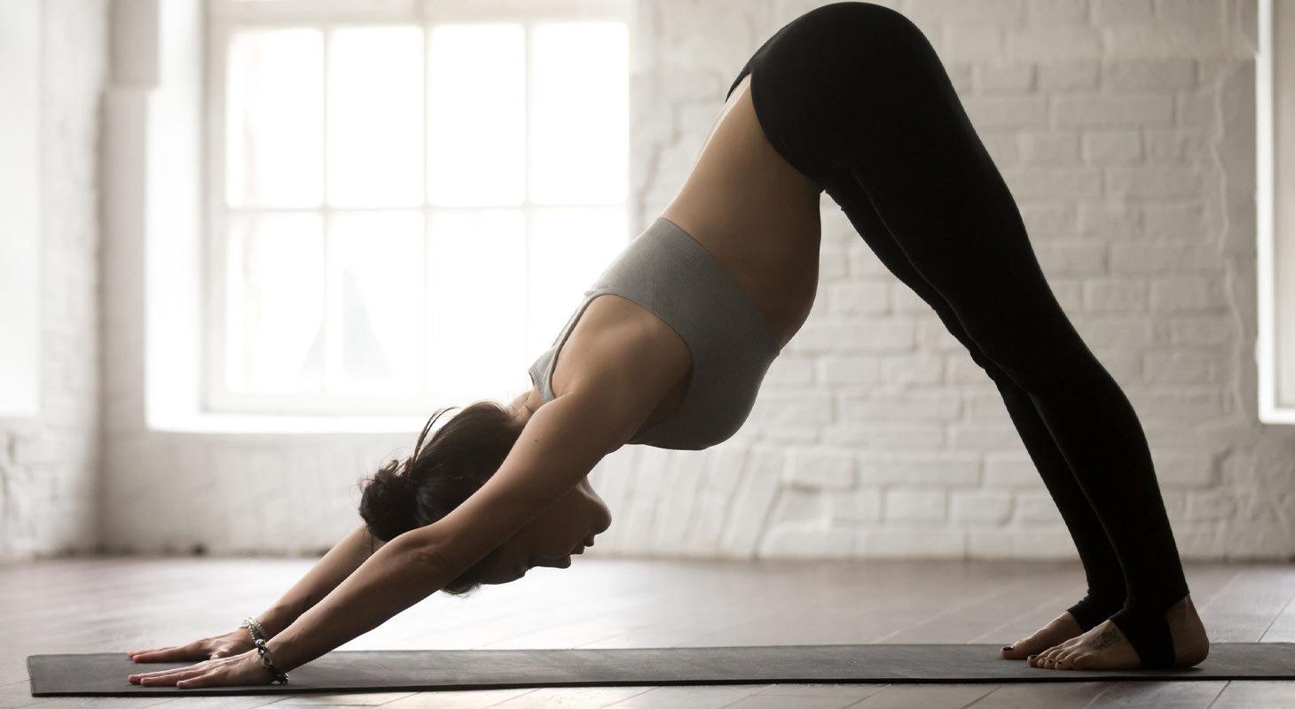 Femme pratiquant le yoga dans la posture du chien tête en bas