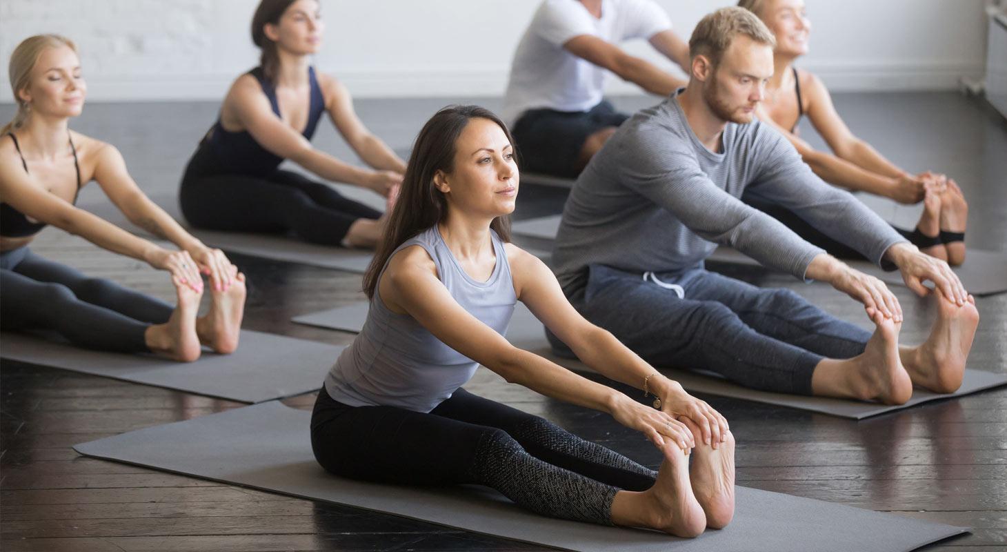 Groupe de jeunes sportifs pratiquant une leçon de yoga avec un instructeur dans une salle de gym