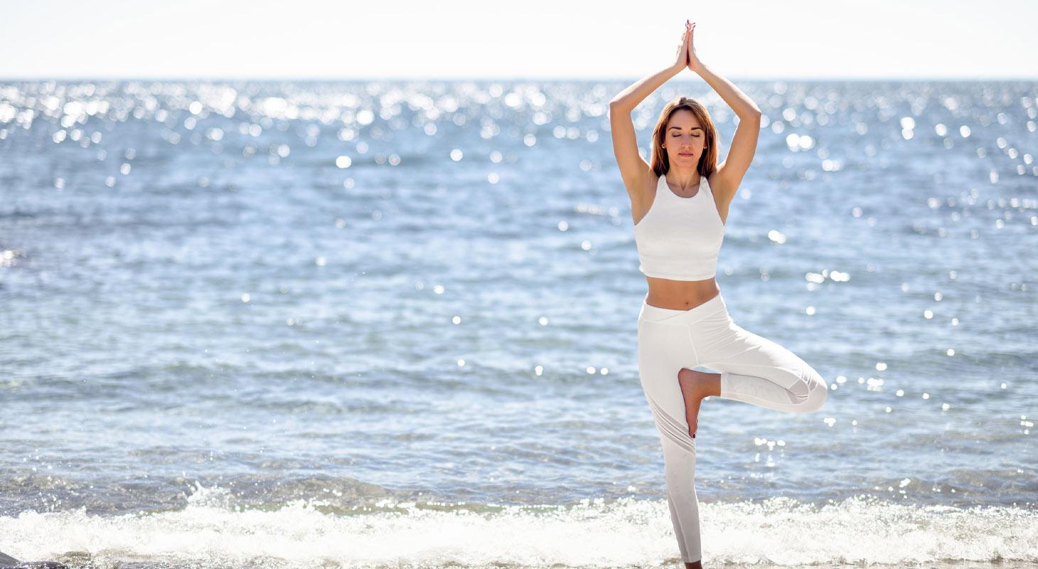 Jeune femme pratiquant le yoga en face de la mer dans la posture de l'arbre en tenue blanche.