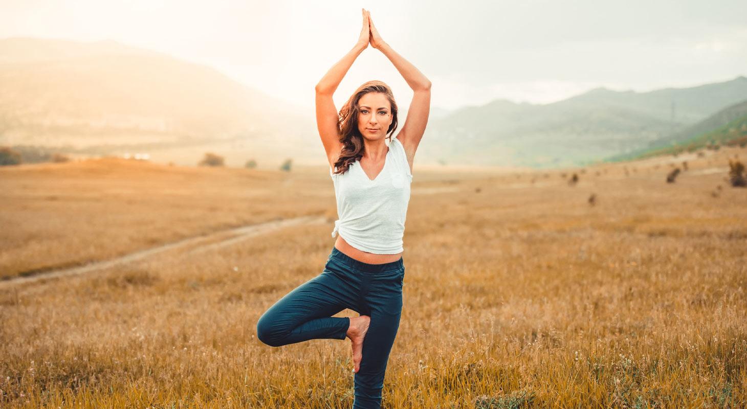 Femme dans un champ pratiquant le yoga dans la posture de l'arbre