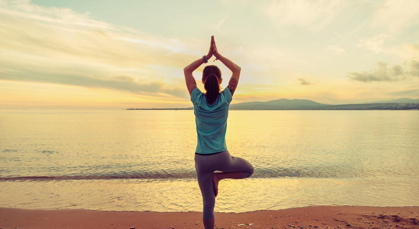eune femme faisant l'exercice de yoga dans la posture de l'arbre sur la plage