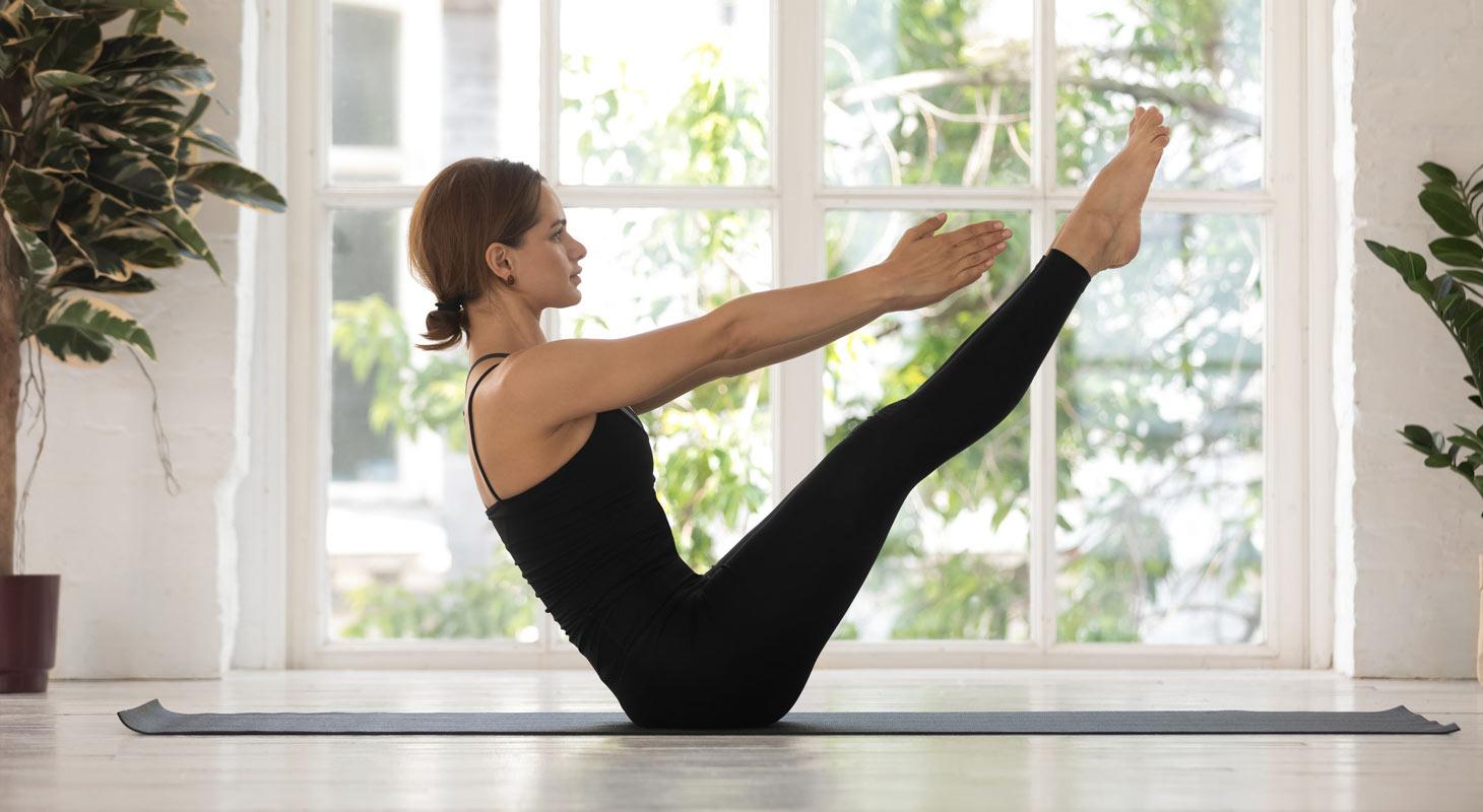 Jeune femme pratiquant le yoga dans la posture du bateau