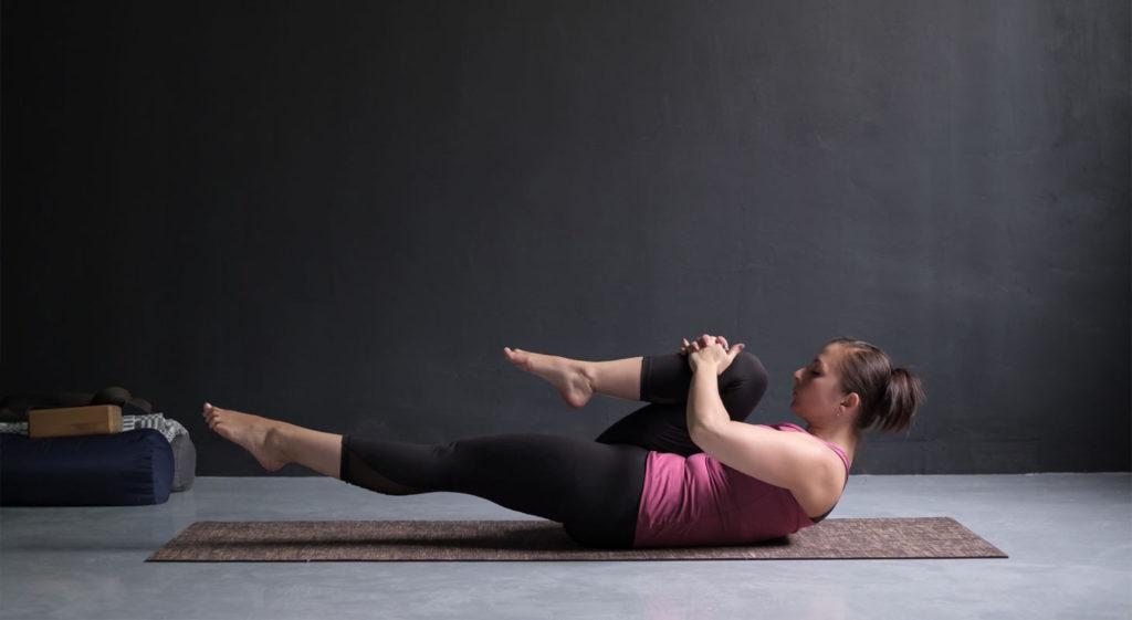 Jeune femme pratiquant le yoga dans la posture de la libération des vents