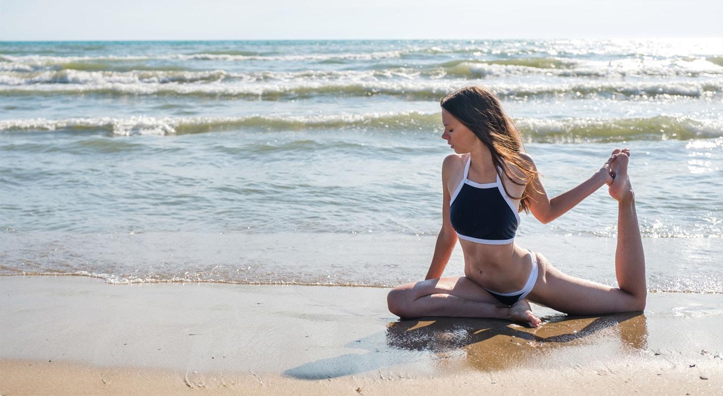 Jeune femme qui pratique la position du pigeon sur la plage face à la mer
