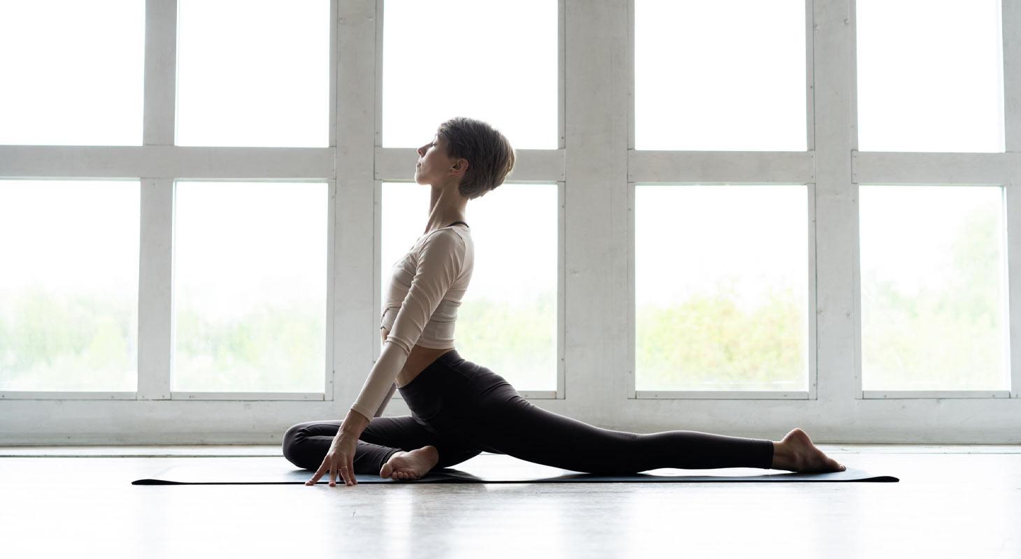 Femme qui pratique le yoga dans la position du pigeon