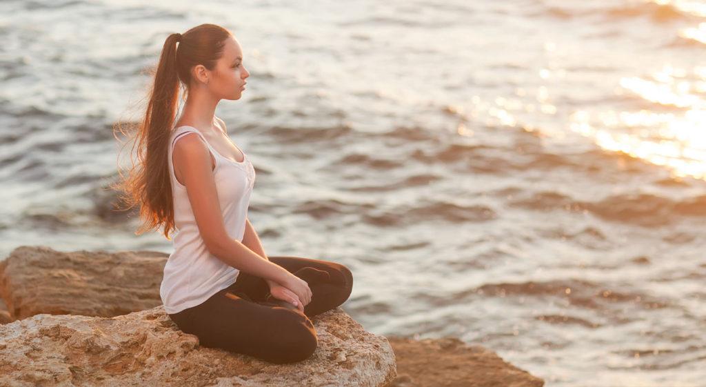Femme dans la position du lotus en face de la mer