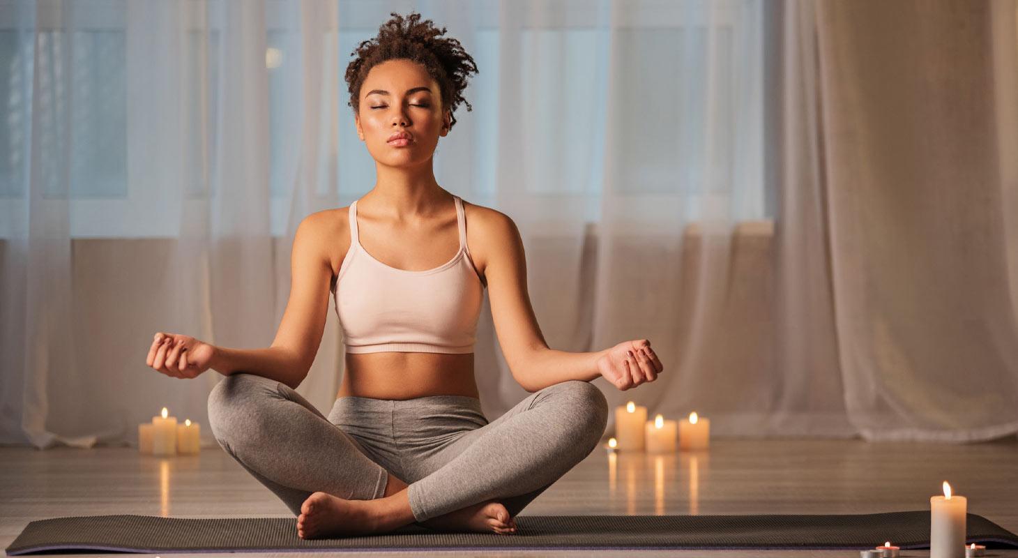 Femme dans la posture du lotus avec des bougies autour d'elle