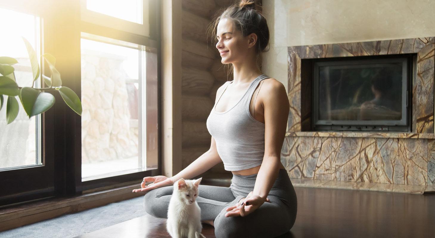 Femme dans la position du lotus avec son chat