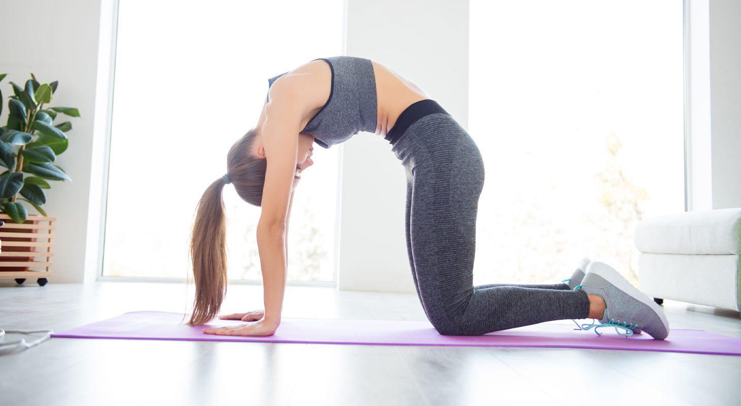 Jeune femme faisant du yoga dans la position du chat dos rond