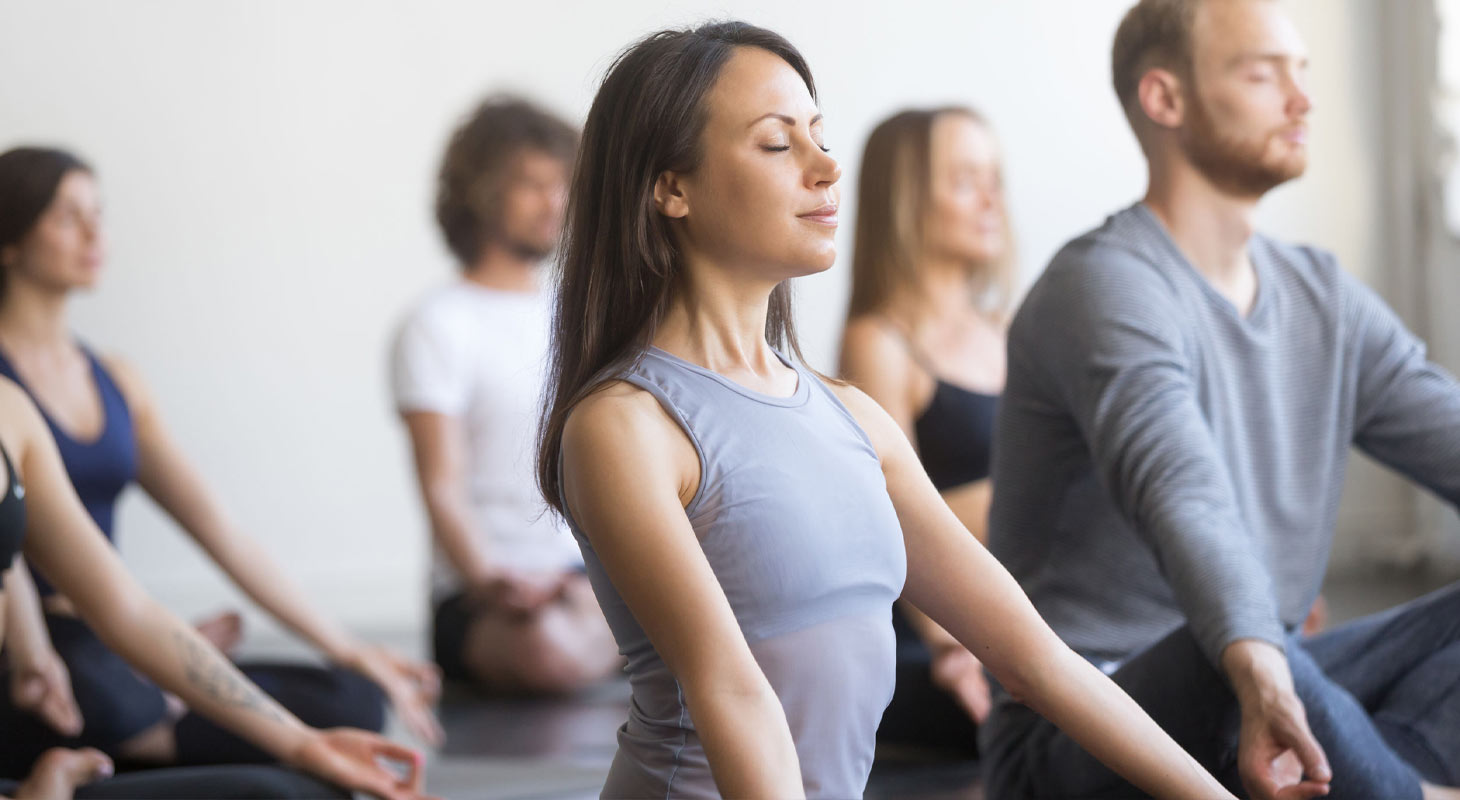 Femme dans un cours de yoga pratiquant une respiration intense