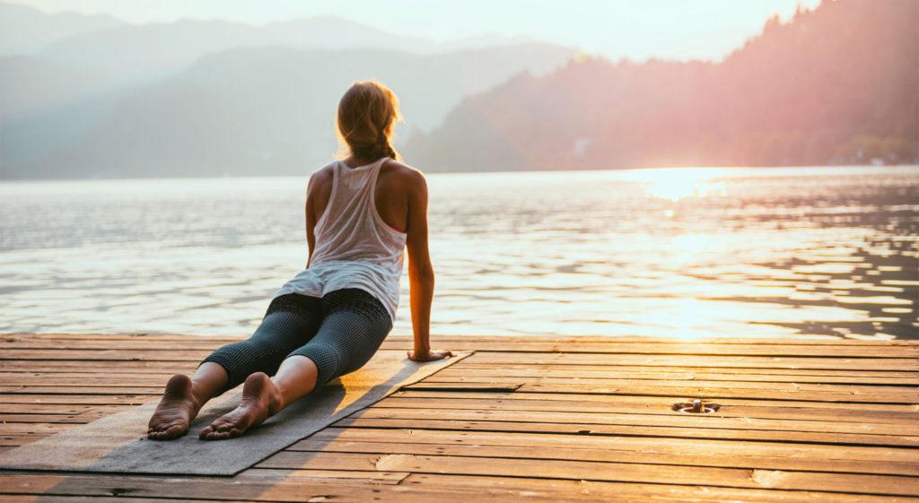 Jeune femme faisant une salutation au soleil en face d'un lac