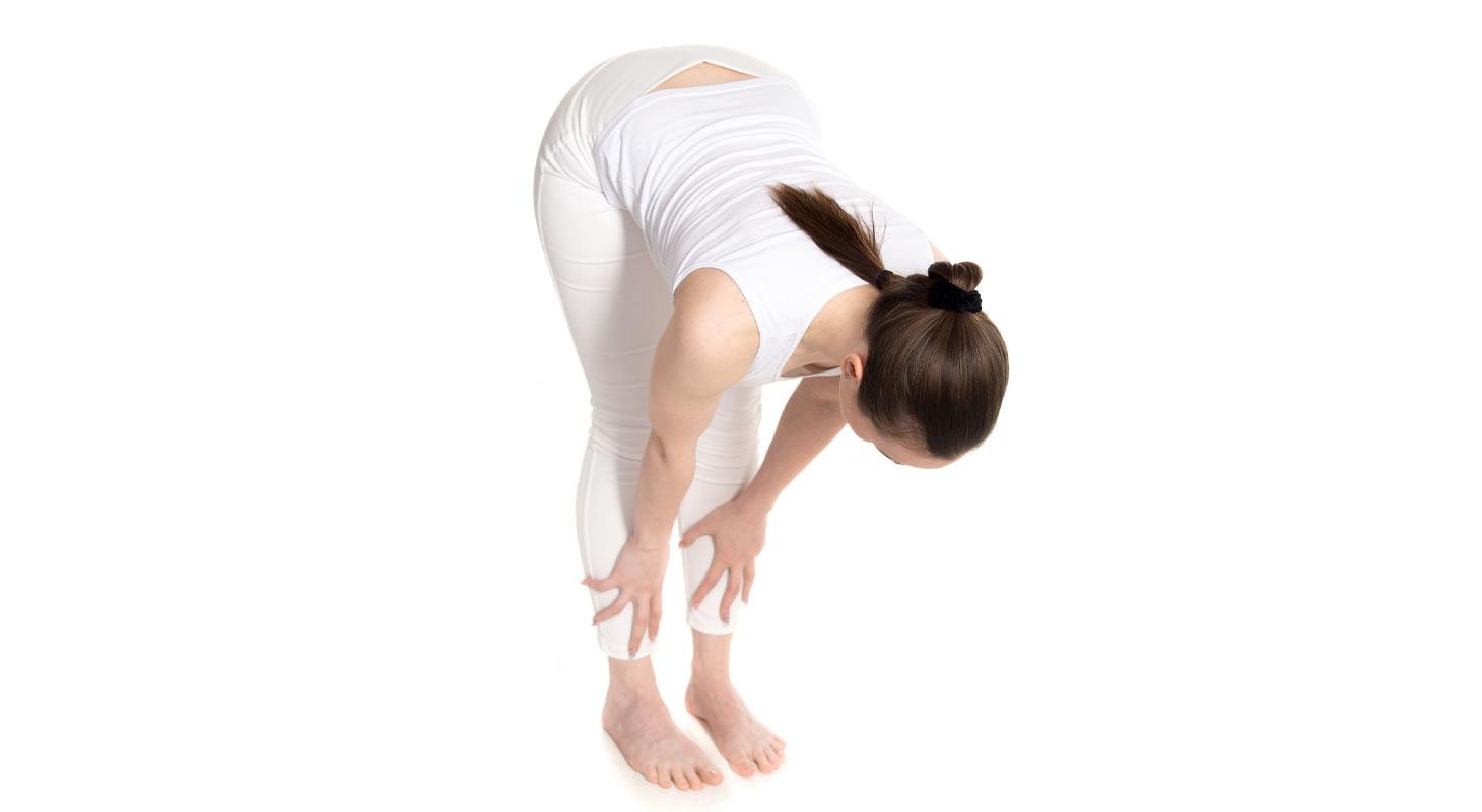 Jeune femme dans la position du Demi-repli vers l'avant – Ardha Uttanasana