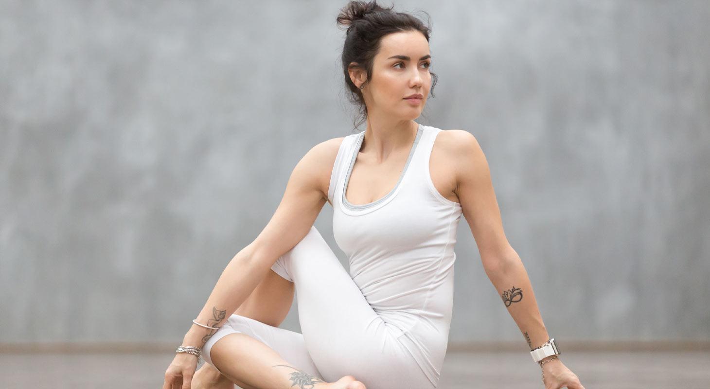 Jeune femme dans la torsion du dos ( Ardha Matsyendrasana )