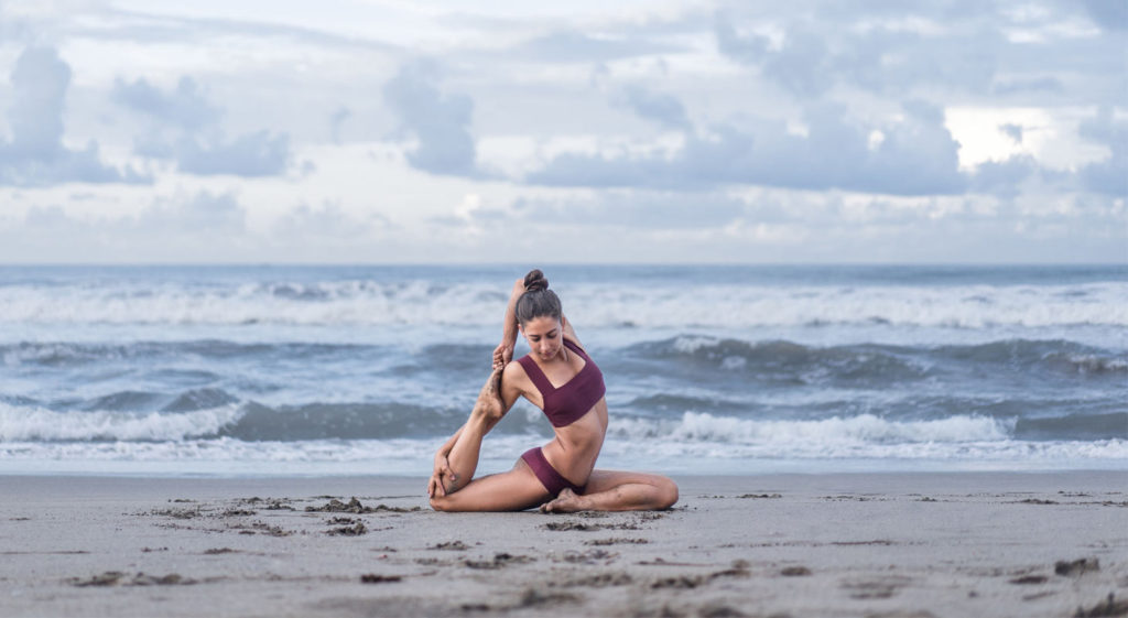 Jeune femme à la plage pratiquant le yoga en posture du roi pigeon
