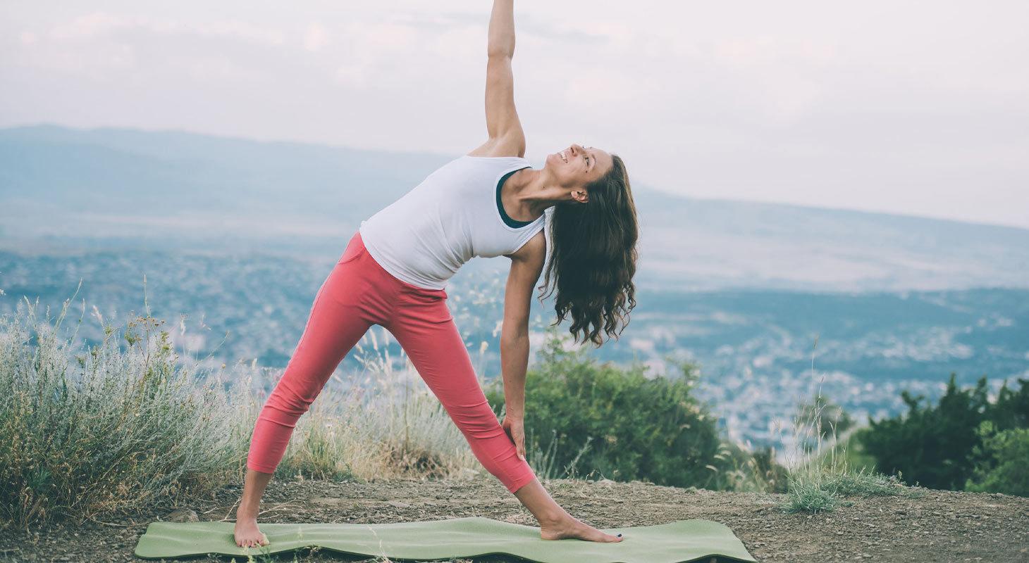 Femme qui fait du yoga dans la nature en face d'une ville