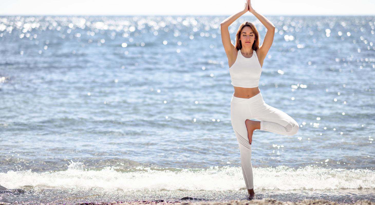 Jeune femme sur la plage dans la posture de l'arbre