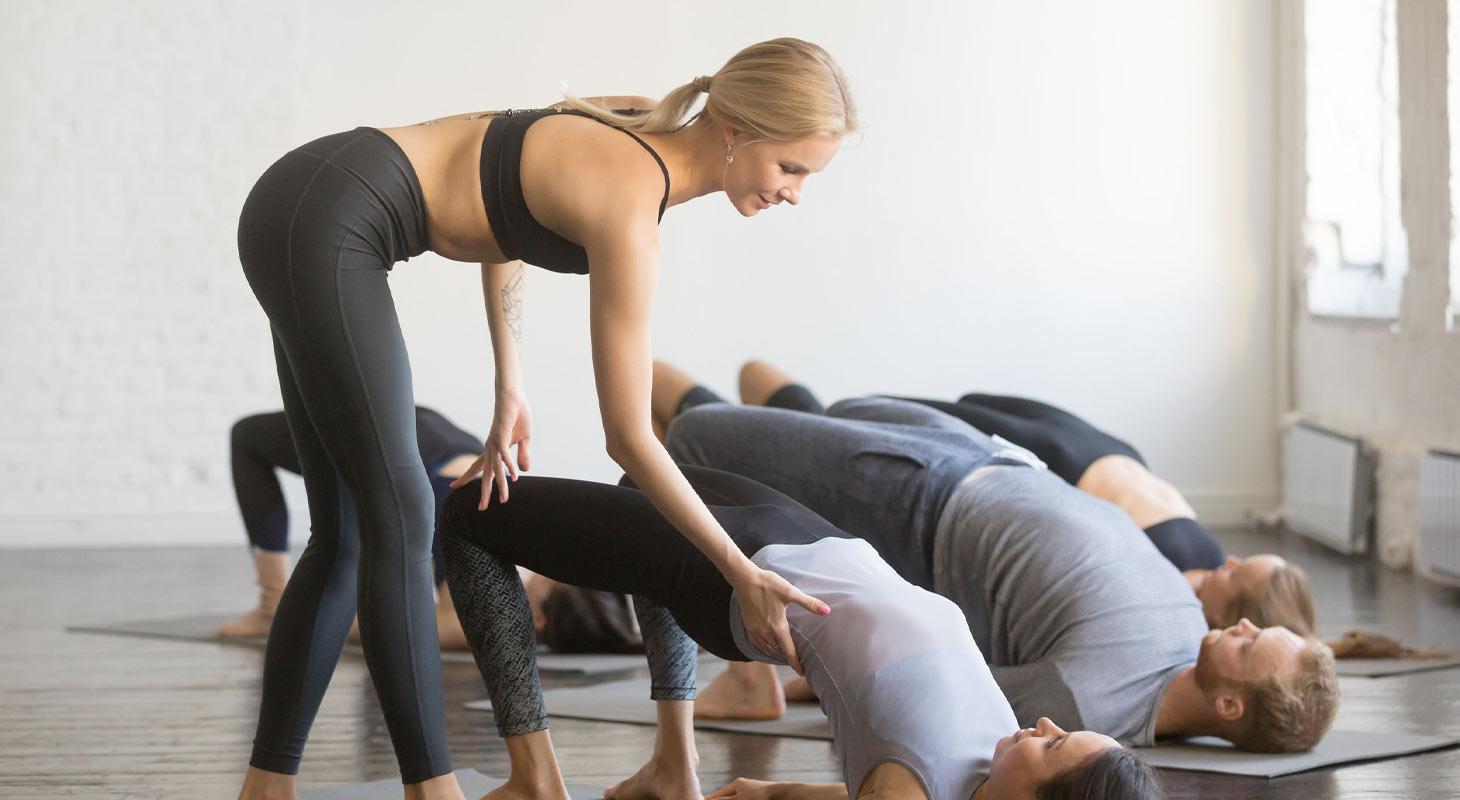 Professeur de yoga avec ses élèves en salle de cours de yoga