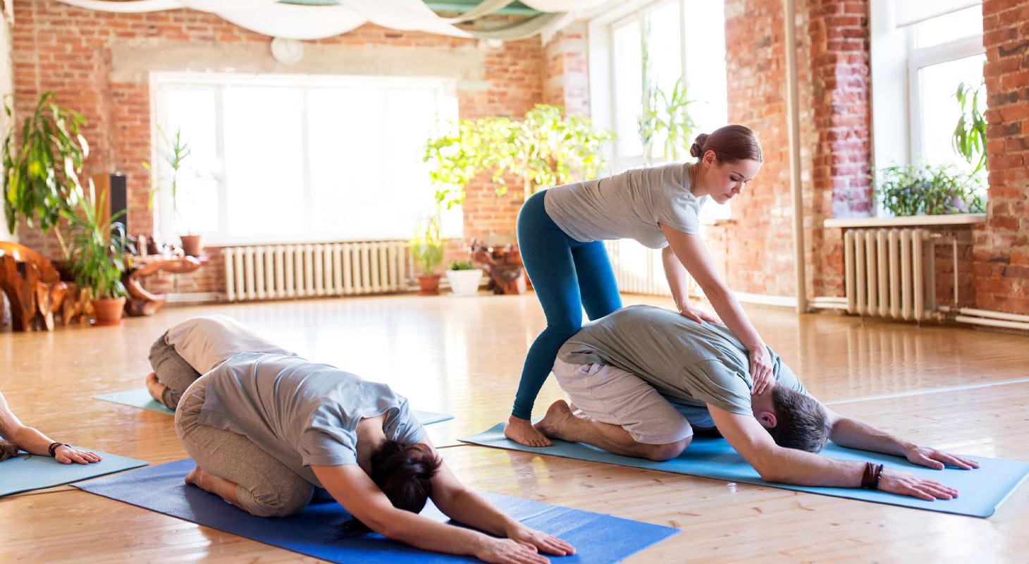 Professeur de yoga corrigeant son élève