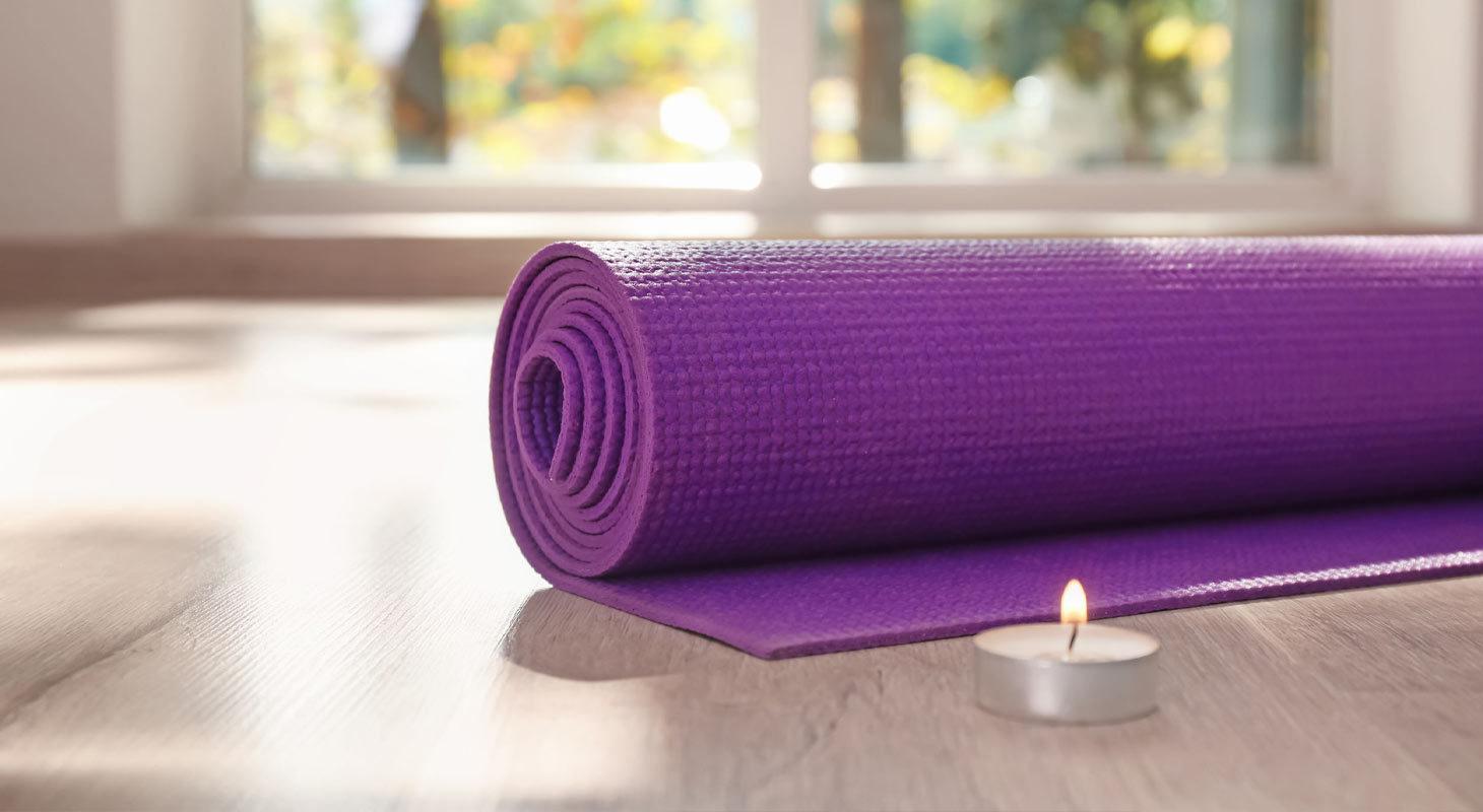 Tapis de yoga violet sur parquet