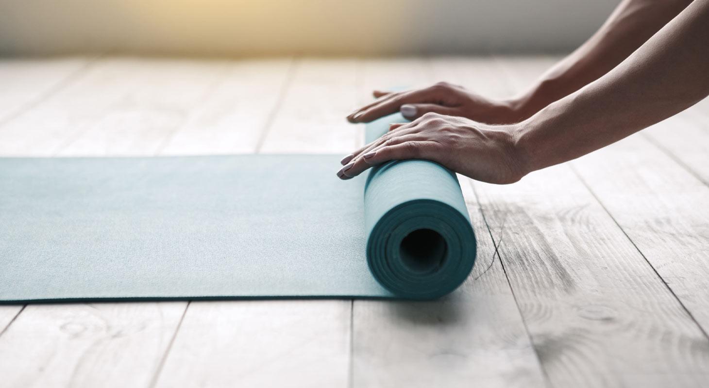 Tapis de yoga bleu en train d'être roulé