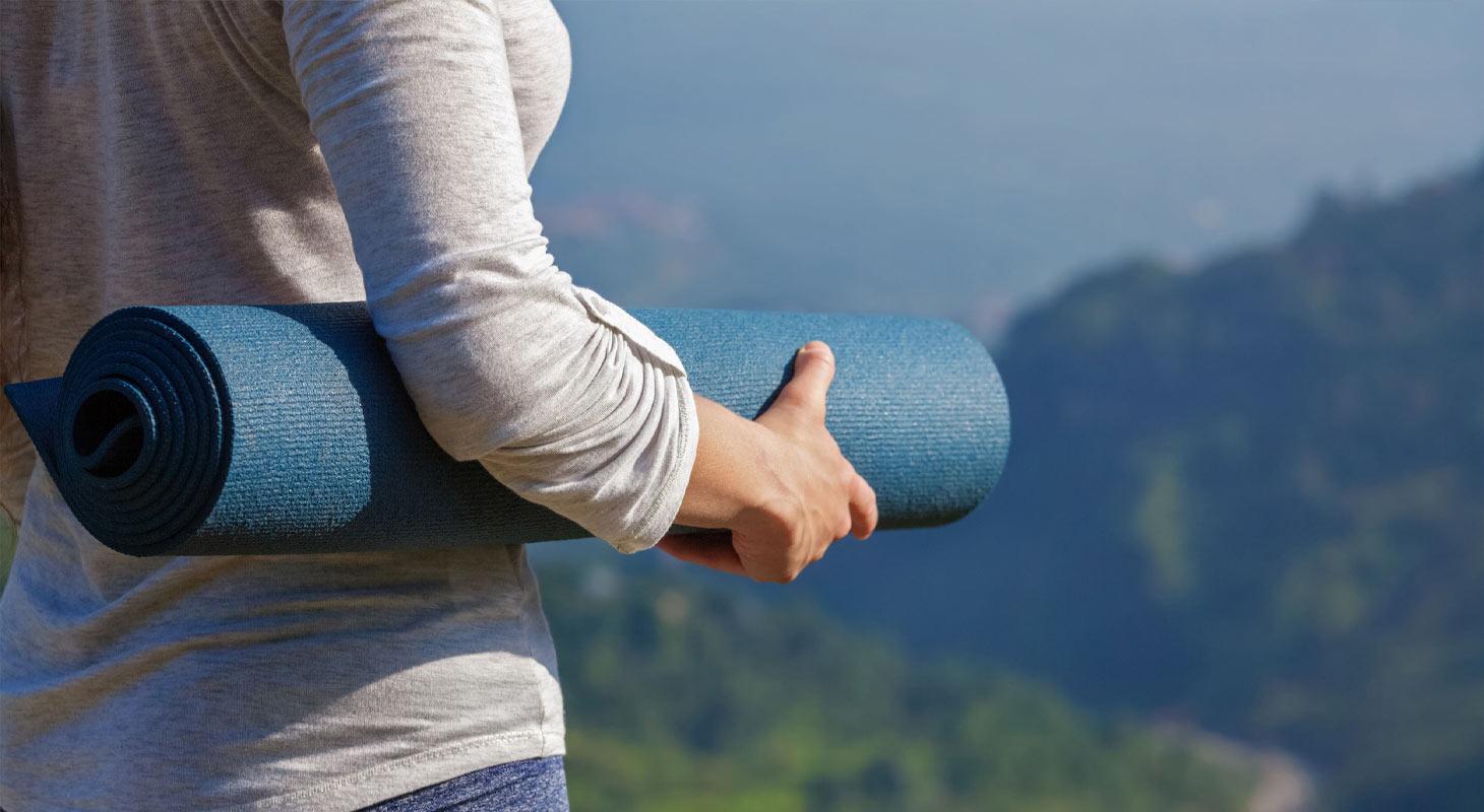 Jeune femme tient un tapis de yoga entre ses bras