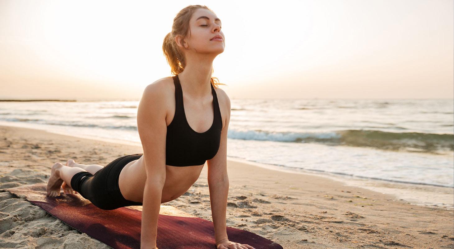 Jeune femme pratique le yoga sur la plage