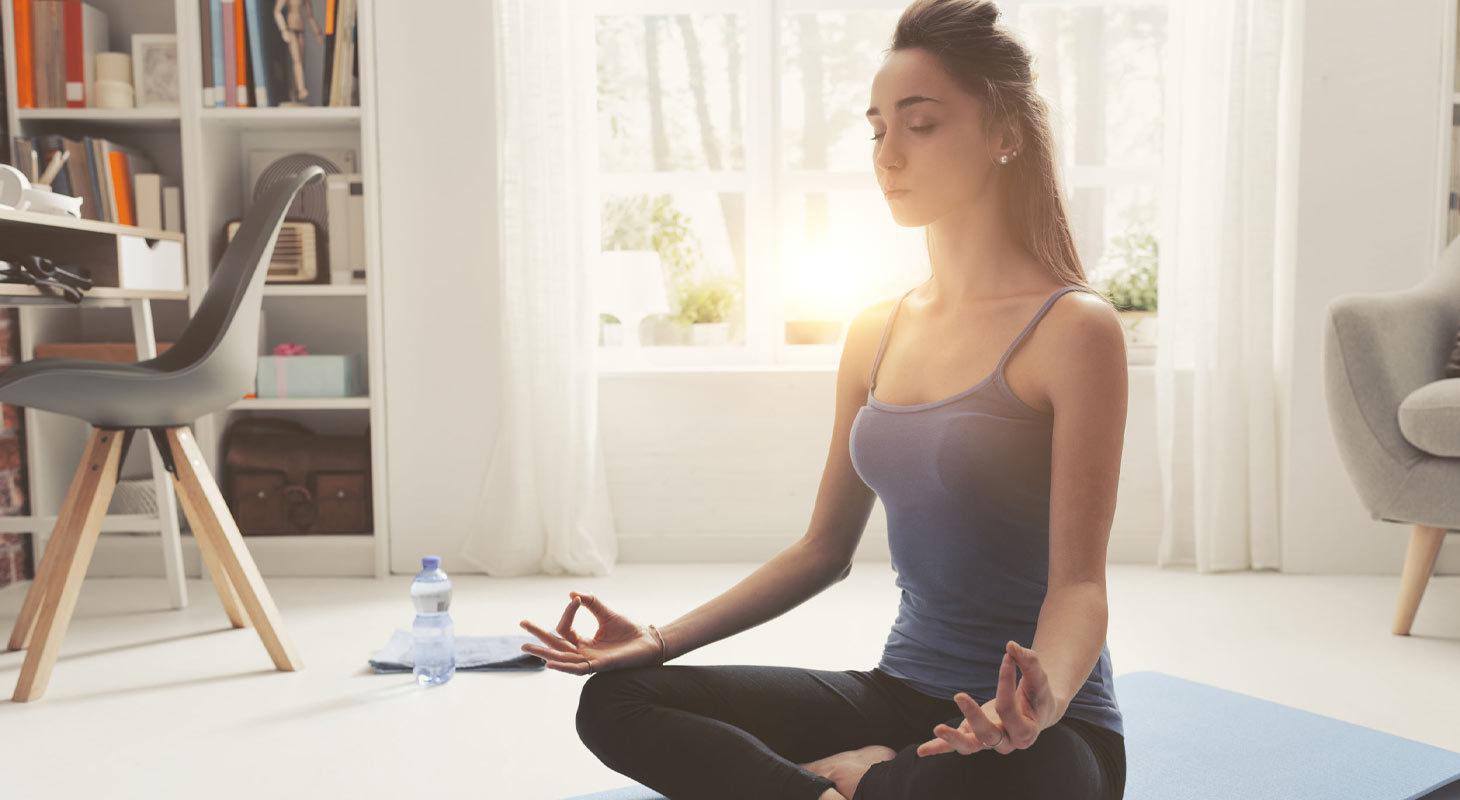 Jeune femme pratique le yoga à la maison