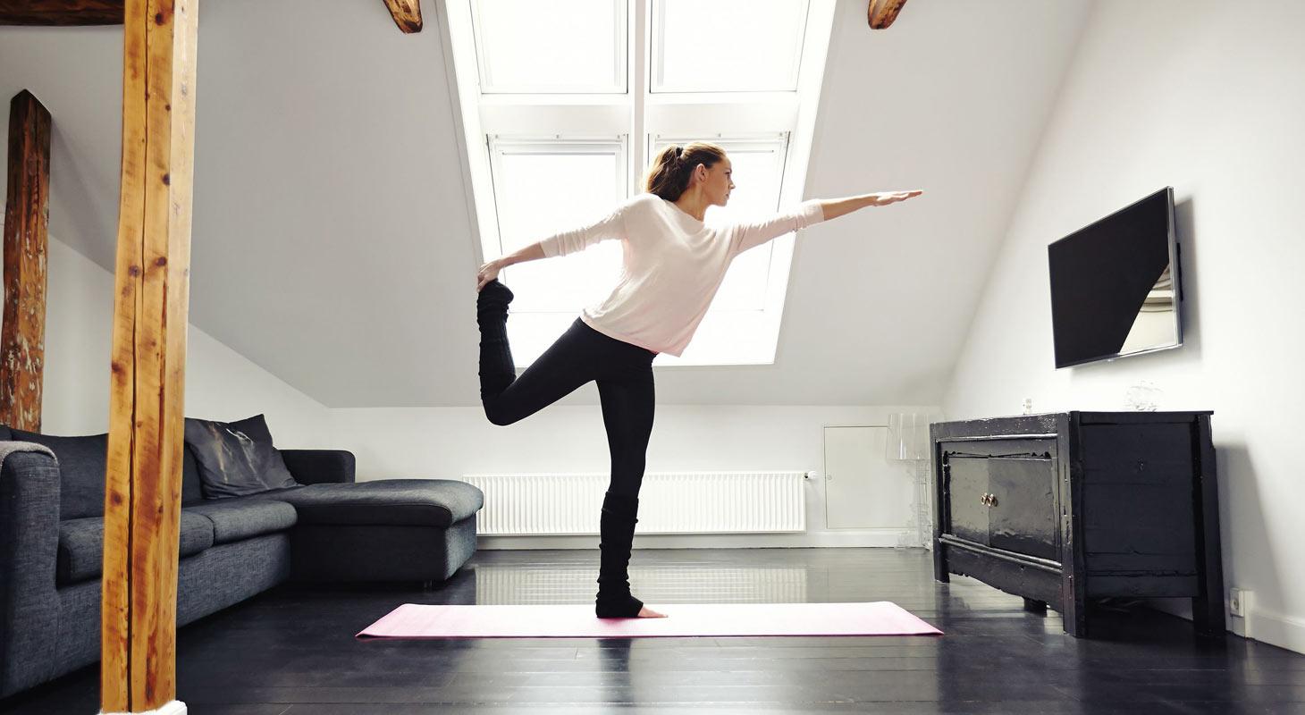 Jeune femme dans la position du danseur chez elle