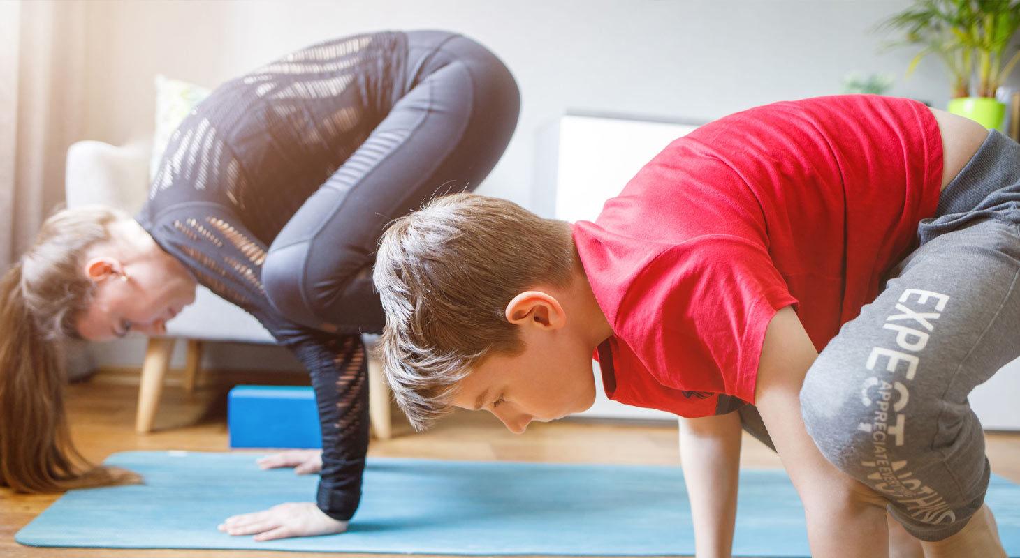 Une femme et un enfant qui s'entraine dans la posture du corbeau en yoga
