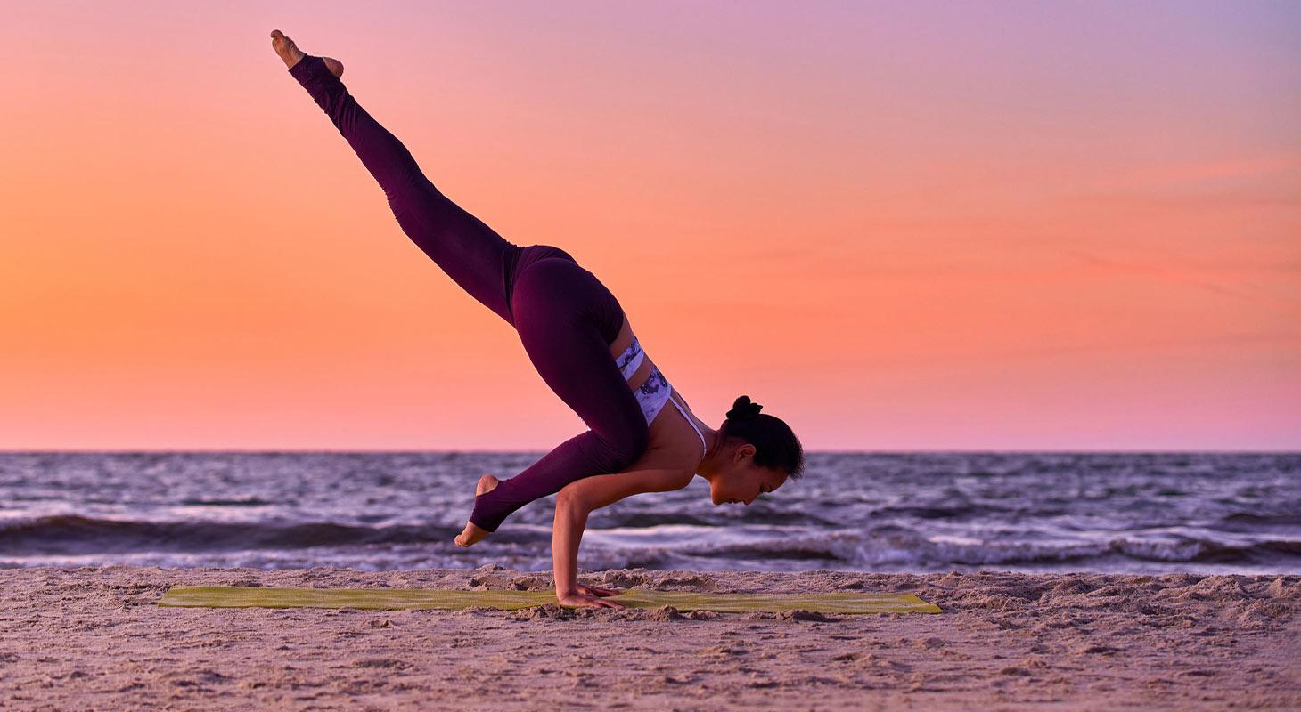 Jeune femme à la plage dans la posture du corbeau en yoga