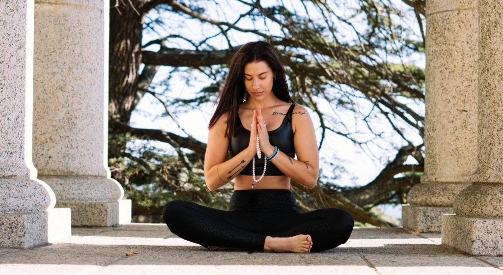 femme pratiquant la position du lotus en exterieur