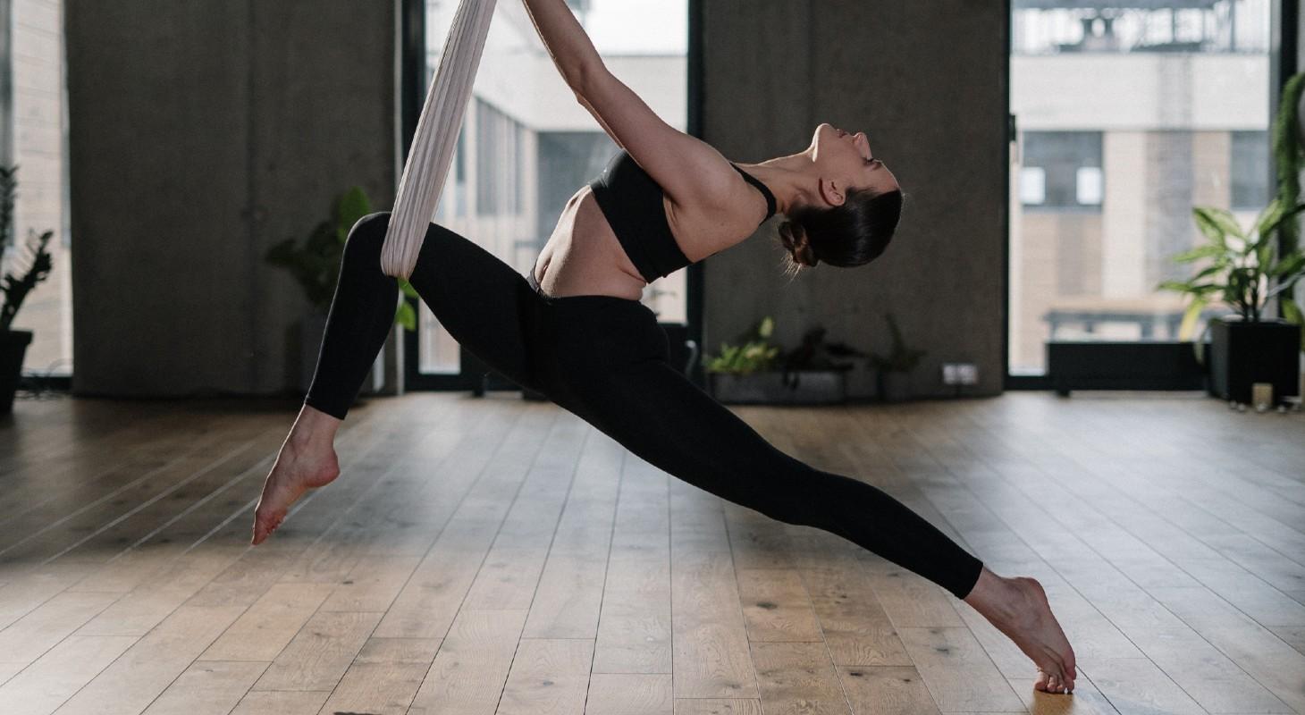 femme pratiquant le yoga aérien