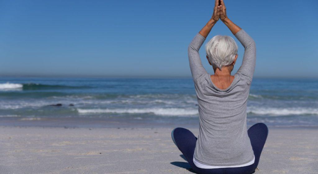 emme sénior pratiquant le yoga sur la plage
