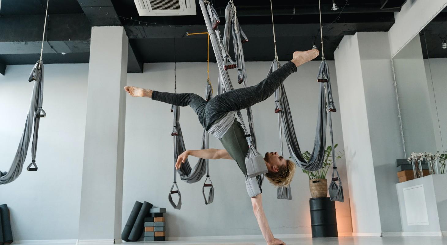 homme pratiquant le yoga aérien