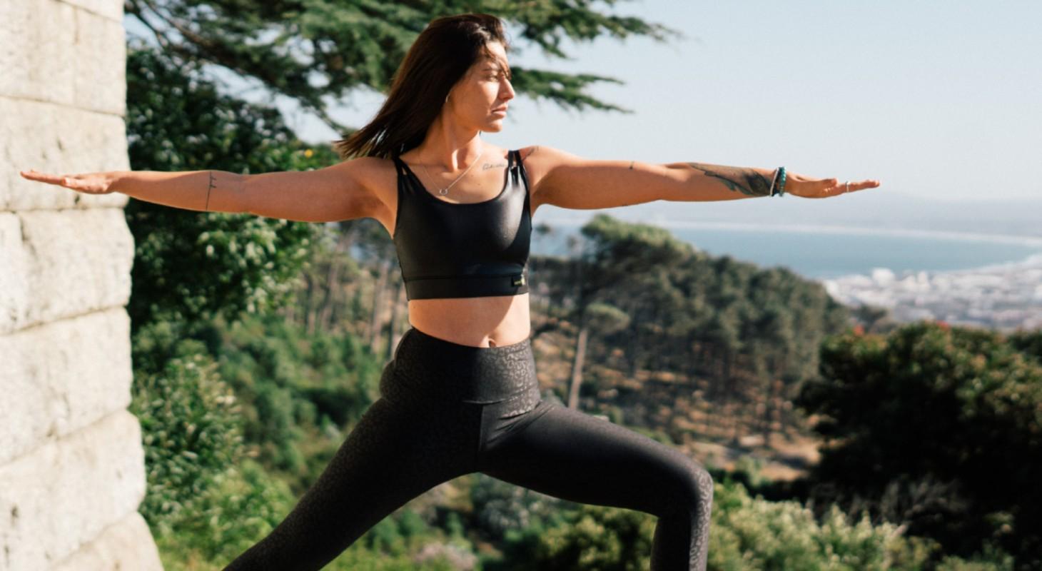 femme en legging noir réalisant la posture de yoga le guerrier