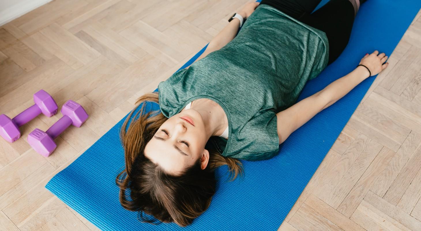 Jeune femme pratiquant du yoga : la posture du cadavre